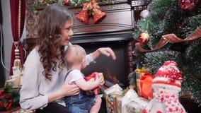 Une jeune mère avec un jeune fils près de la cheminée habillant un arbre de Noël Joyeux Noël et bonnes fêtes clips vidéos