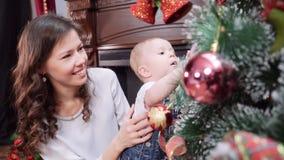 Une jeune mère avec un jeune fils près de la cheminée habillant un arbre de Noël Joyeux Noël et bonnes fêtes banque de vidéos
