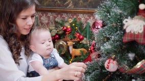 Une jeune mère avec un petit fils dans une chambre près de la cheminée habillant un arbre de Noël clips vidéos