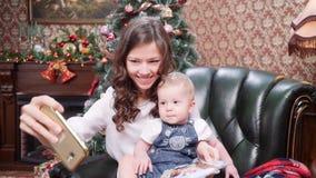Une jeune mère avec un petit fils fait le selfie sur un smartphone près d'un arbre de Noël Joyeux Noël et bonnes fêtes clips vidéos