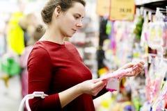 Une jeune mère dans le magasin choisit les marchandises pour l'enfant Belle femme dans un supermarché avec un panier à provisions Image stock
