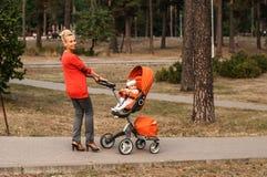 Une jeune mère de sourire porte une poussette orange avec un bébé en parc photo libre de droits