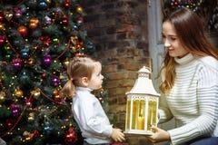 Une jeune mère et sa fille allument des bougies dans une salle confortable le réveillon de Noël Photos libres de droits