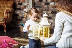 Une jeune mère et sa fille allument des bougies dans une salle confortable le réveillon de Noël Photographie stock libre de droits