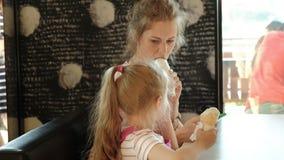 Une jeune mère et sa petite fille passent le temps dans un restaurant lentement Consommation de la crême glacée banque de vidéos