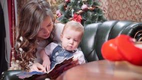 Une jeune mère lit des contes de Noël à son jeune fils Joyeux Noël et bonnes fêtes clips vidéos