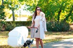 Une jeune mère marche avec un enfant par temps chaud photographie stock