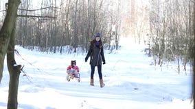 Une jeune mère porte sa fille sur un traîneau clips vidéos