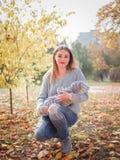 Une jeune mère, s'accroupissant en parc d'automne et tenant un joli bébé dans des ses bras image stock
