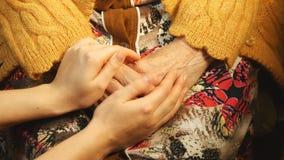 Une jeune main soulageant une vieille paire de mains banque de vidéos