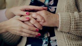 Une jeune main touche et tient une vieille main froissée Petite-fille tenant une main du ` s de grand-mère banque de vidéos