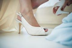 Une jeune mariée à être est aidée avec ses chaussures en vue de elle nous Image stock
