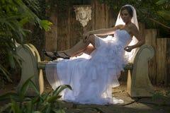 Une jeune mariée avec le hairlight se reposant sur un banc concret photographie stock