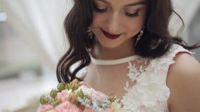 Une jeune jeune mariée dans une robe l'épousant admire un bouquet l'épousant Plan rapproché banque de vidéos