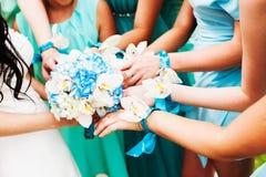 Une jeune mariée et ses demoiselles d'honneur tenant des fleurs Image stock
