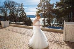 Une jeune mariée mince marche le long de la rue et apprécie la chaleur du soleil et du ciel bleu Air frais et la beauté de Photo libre de droits