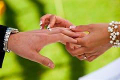 Une jeune mariée place un anneau sur les mariés remettent photographie stock