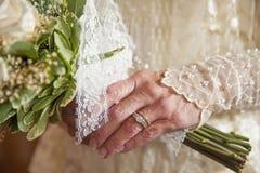 Une jeune mariée plus âgée tient des fleurs Photographie stock libre de droits
