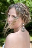 Une jeune mariée regarde en arrière au-dessus de son épaule. Image libre de droits