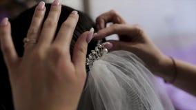 Une jeune mari?e au salon de coiffure faisant ?pouser les pr?parations, mains de styliste touchant ses cheveux barre Fermez-vous  images stock