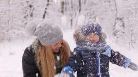 Une jeune mère et son fils jouant avec la neige dans la forêt d'hiver banque de vidéos