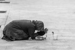 Une jeune pauvre femme priant sur un trottoir près du centre de la ville de Bucarest Photo stock