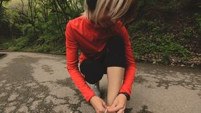 Une jeune séance caucasienne de fille lie ses dentelles avant de pulser sur un chemin forestier dans le Caucase orientation vers  banque de vidéos