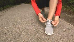 Une jeune séance caucasienne de fille lie ses dentelles avant de pulser sur un chemin forestier dans le Caucase orientation vers  clips vidéos