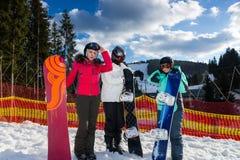 Une jeune société des personnes dans des costumes de ski se tenant avec des surfs des neiges Photos stock