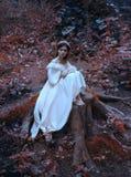 Une jeune, triste princesse avec les cheveux très longs s'assied sur un grand tronçon d'un vieil arbre et attend son prince La fi photographie stock libre de droits