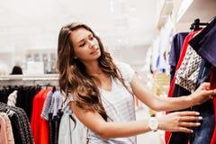 Une jolie dame jeune avec de longs cheveux, vêtements sport de port, choisit une nouvelle robe dans un magasin célèbre images libres de droits