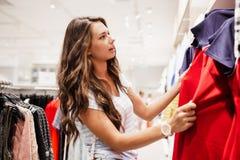 Une jolie dame jeune avec de longs cheveux, vêtements sport de port, choisit une nouvelle robe dans un magasin célèbre photographie stock