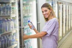 Une jolie eau de achat de sourire de femme blonde Images stock