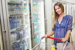 Une jolie femme blonde de sourire achetant les produits congelés Photographie stock