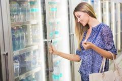 Une jolie femme blonde de sourire achetant les produits congelés Image libre de droits