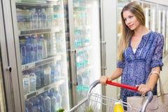 Une jolie femme blonde de sourire achetant les produits congelés image stock