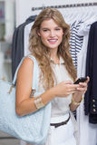 Une jolie femme blonde de sourire regardant son smartphone Photo libre de droits