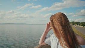 Une jolie fille apprécie une soirée chaude d'été et touche souvent ses cheveux clips vidéos