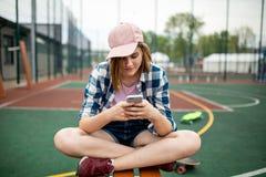 Une jolie fille blonde portant la chemise à carreaux, le chapeau rose et les caleçons de denim s'assied en tailleur sur le champ  photo stock