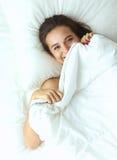 Une jolie jeune femme jetant un coup d'oeil de dessous les couvertures Photos stock