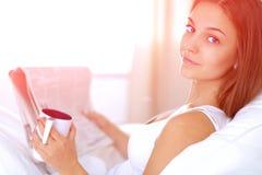 Une jolie jeune femme s'asseyant dans le lit sous la couverture images libres de droits