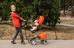 Une jolie mère marche en parc et porte une poussette orange avec un bébé photo stock