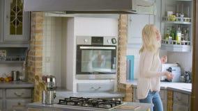 Une joyeuse femme entre dans la cuisine en dansant et en brandissant clips vidéos
