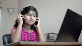 Une joyeuse jeune fille asiatique vêtue d'un casque et écoutant de la musique sur un ordinateur portable, dansant et chantant clips vidéos