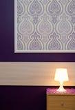 Une lampe avec le papier peint violet Photographie stock libre de droits