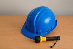 Une lampe-torche en plastique jaune et bleue avec un isolat bleu de casque antichoc Images stock