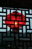 Une lanterne rouge derrière l'hublot chinois Photographie stock libre de droits