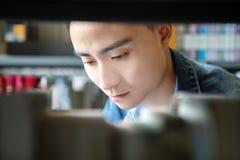 Une lecture asiatique d'homme dans une bibliothèque Photo stock