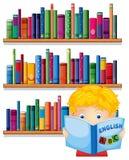 Une lecture de garçon avec étagères en bois au fond Images stock