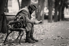 Une lecture sans abri sur un banc Photos libres de droits